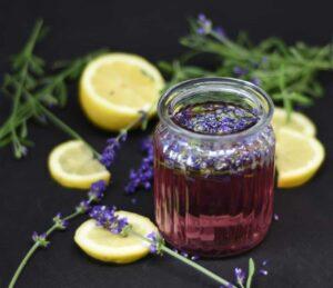 Ein Gläschen mit Lavendelsirup umgeben von frischen Lavendelblüten und Zitronenscheiben